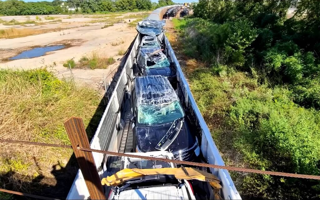 A train carrying cars is razed by a bridge